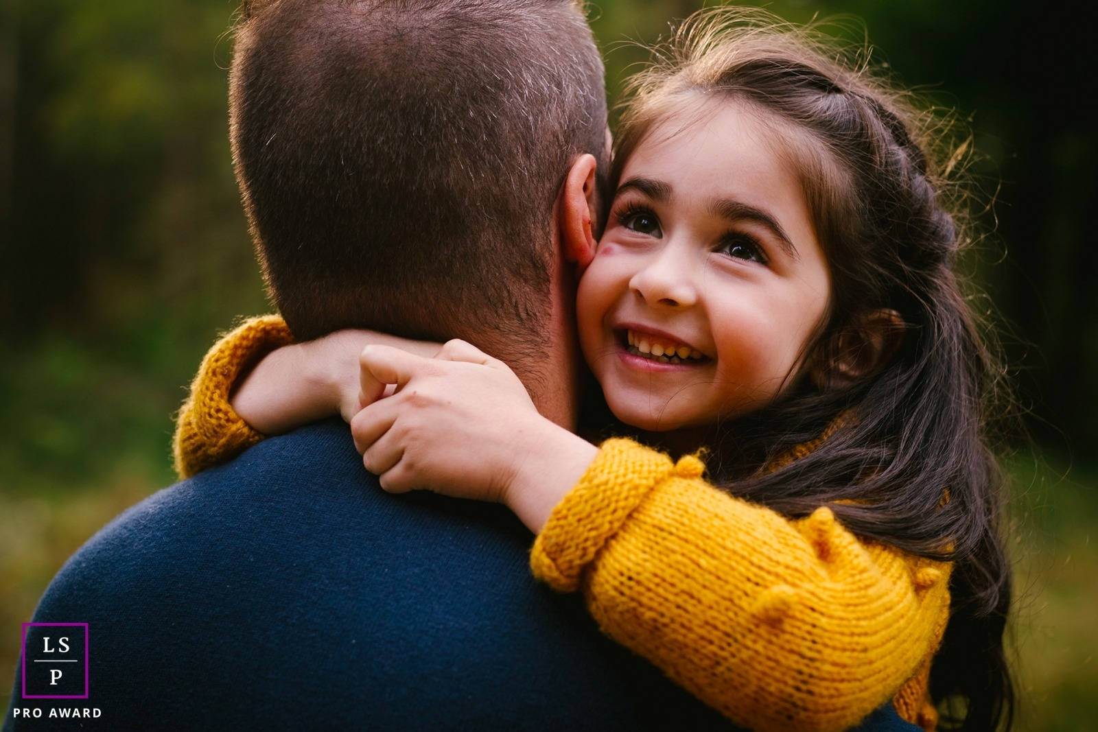 petite fille dans les bras de son papa au lever du soleil dans la foret