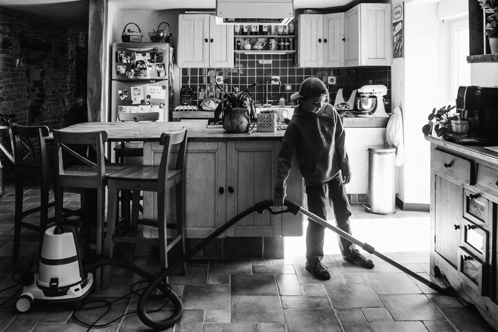 enfant passant l'aspirateur dans la cuisine