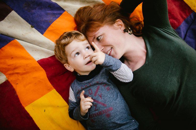 une maman et son fils allongés sur une couverture colorée
