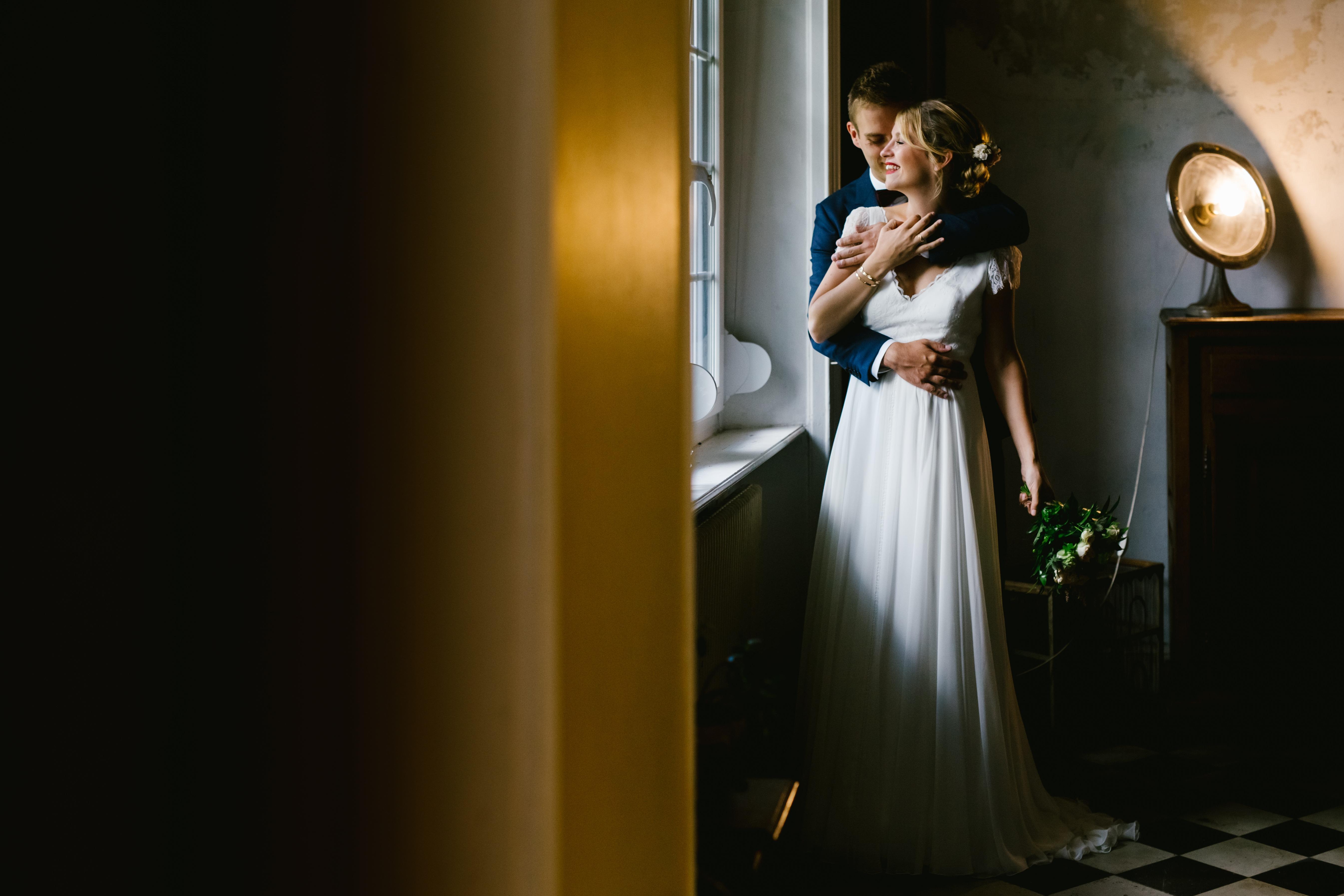couple devant une fenêtre avant la cérémonie