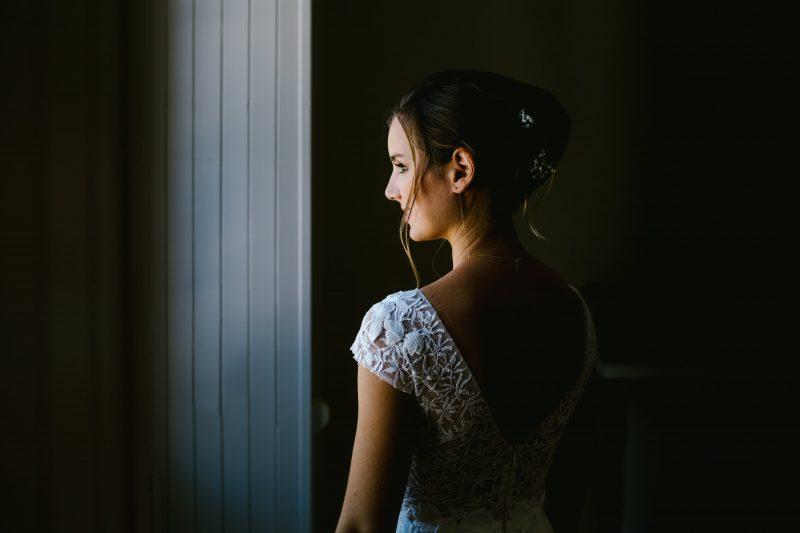 la mariée est prête à partir portrait devant une fenêtre