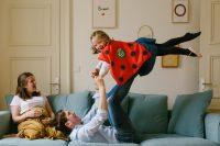 famille sur un canapé enfants qui vole sur les pieds de son papa avec une cape