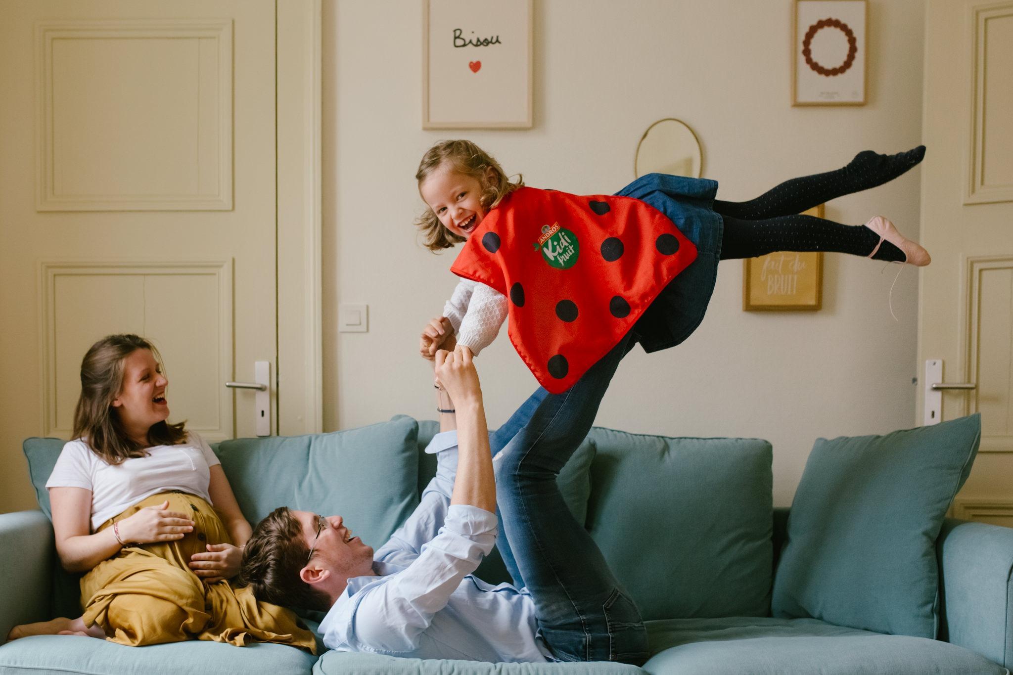 photo famille dans le canape faire l'avion avec papa