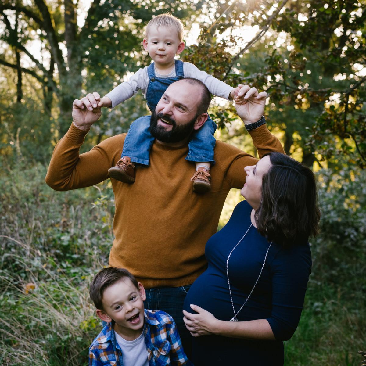 une famille avec deux petits garçons joue ensemble et attendent un bébé