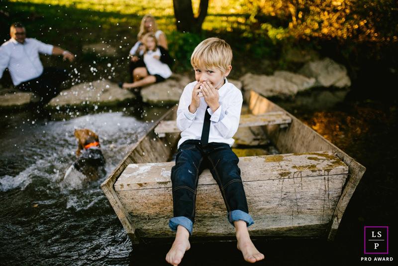 un garçon sur une barque le chien saute à l'eau