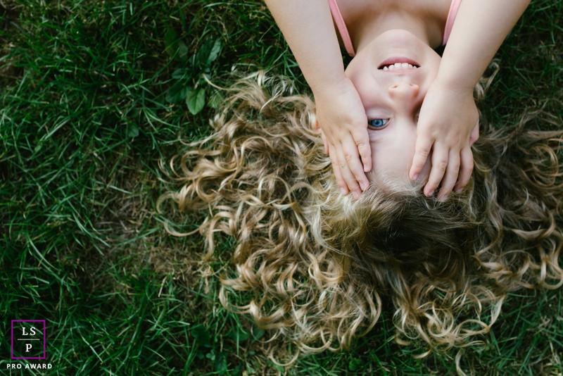 portrait petite fille cachée derrière ses mains et allongée dans l'herbe