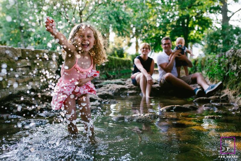 une petite fille m'éclabousse les pieds dans un cours d'eau
